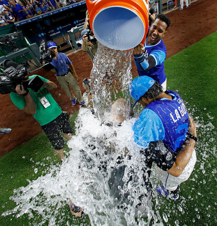 . Kansas City Royals\' Salvador Perez douses Adalberto Mondesi and television commentator Joel Goldberg after the team\'s baseball game against the Cleveland Indians on Saturday, Aug. 25, 2018, in Kansas City, Mo. The Royals won 7-1. (AP Photo/Charlie Riedel)