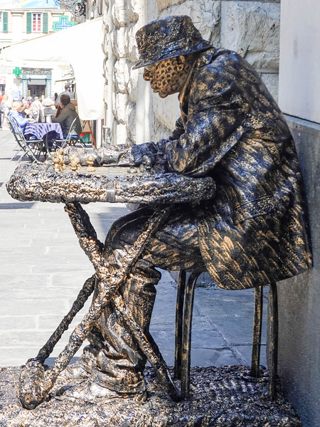 Statue of man playing chess in Genoa, Italy.