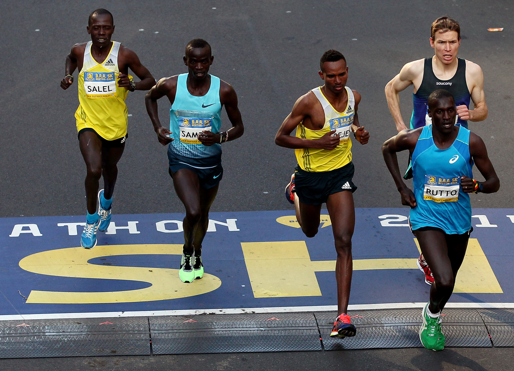 . (L-R) Daniel Salel of Kenya, Stephen Sambu of Kenya, Dejen Gebremeskel of Ethiopia, Ben True of the United States, and Lani Rutto of Kenya crosh the finish line of the Boston Marathon as part of the 2014 B.A.A. 5K race course on April 19, 2014 in Boston, Massachusetts.  (Photo by Alex Trautwig/Getty Images)