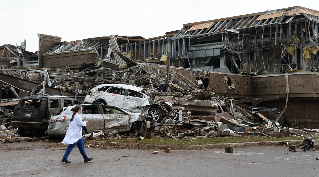 . A nurse walks by of what is left of a Moore hospital after being hit by a tornado that destroyed buildings and overturned cars.  A huge tornado with winds of up to 200 miles per hour (320 kph) devastated the Oklahoma City suburb of Moore on Monday, ripping up at least two elementary schools and a hospital and leaving a wake of tangled wreckage.  