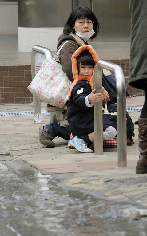 . A mother and child crouch on a street in Tokyo while an earthquake hits Friday, March 11, 2011. Japan was struck by a magnitude-8.8 earthquake off its northeastern coast Friday, triggering a 13-foot (4-meter) tsunami that washed away cars and tore away buildings along the coast near the epicenter.(AP Photo/Kyodo News)