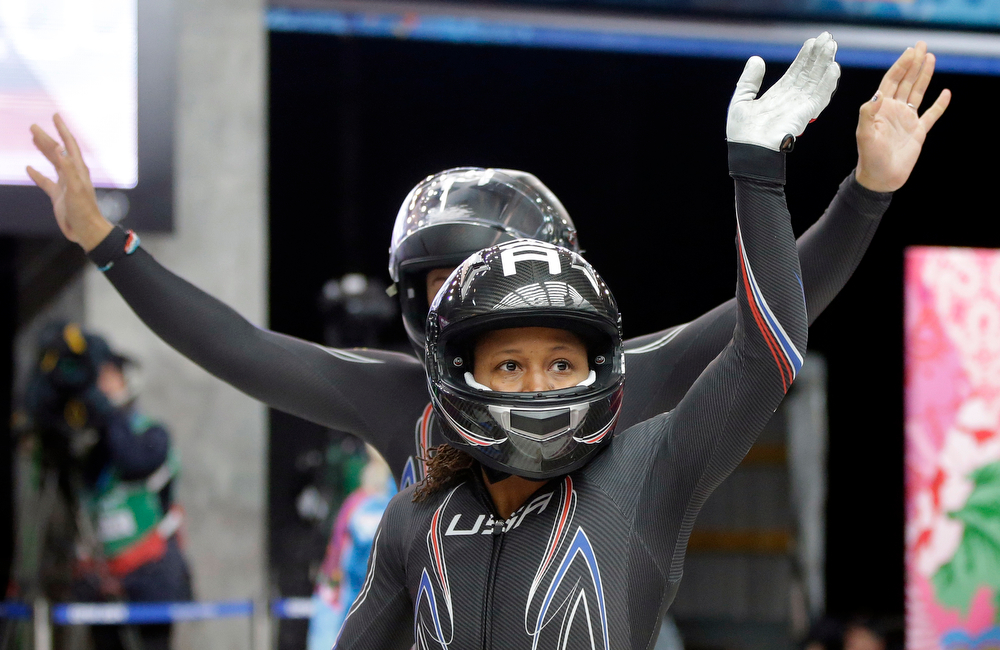 . The team from the United States USA-1, piloted by Elana Meyers with brakeman Lauryn Williams, front, wave to fans after their first run during the women\'s two-man bobsled competition at the 2014 Winter Olympics, Tuesday, Feb. 18, 2014, in Krasnaya Polyana, Russia. (AP Photo/Dita Alangkara)