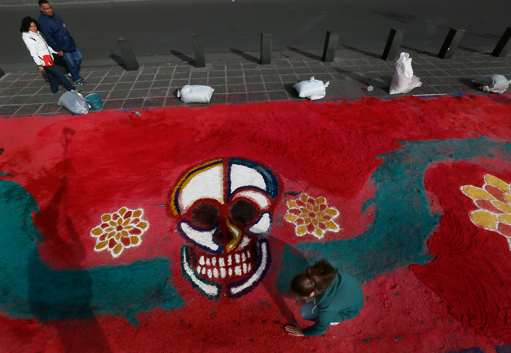 . A couple walks by as a woman works on a sawdust representation of a skull as part of the Day of the Dead festivities in Mexico City, Thursday, Oct. 27, 2016.  The holiday honors the dead as friends and families gather in cemeteries to decorate their loved ones\' graves and hold vigil through the night on Nov. 1 and 2. (AP Photo/Marco Ugarte)