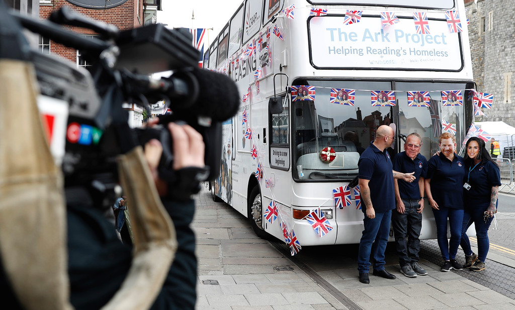 . Volunteers from a homeless charity pose for a television crew wearing masks of Prince Philip, second left, Prince Harry and Meghan Markle next to the charity\'s bus which is outside the walls of Windsor Castle, in Windsor, England, Wednesday, May 16, 2018. Preparations continue in Windsor ahead of the royal wedding of Britain\'s Prince Harry and Meghan Markle on Saturday. (AP Photo/Alastair Grant)