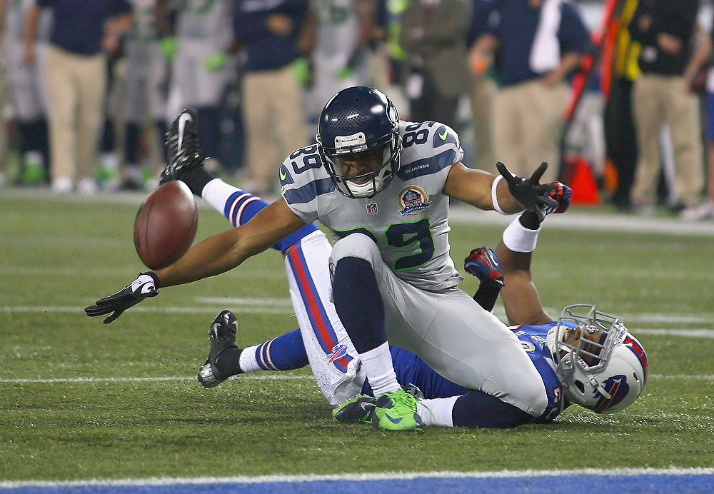 . Doug Baldwin #89 of the Seattle Seahawks loses control of the ball after being hit by Justin Rogers #26 of the Buffalo Bills at Rogers Centre on December 16, 2012 in Toronto, Ontario.Seattle won 50-17.  (Photo by Rick Stewart/Getty Images)