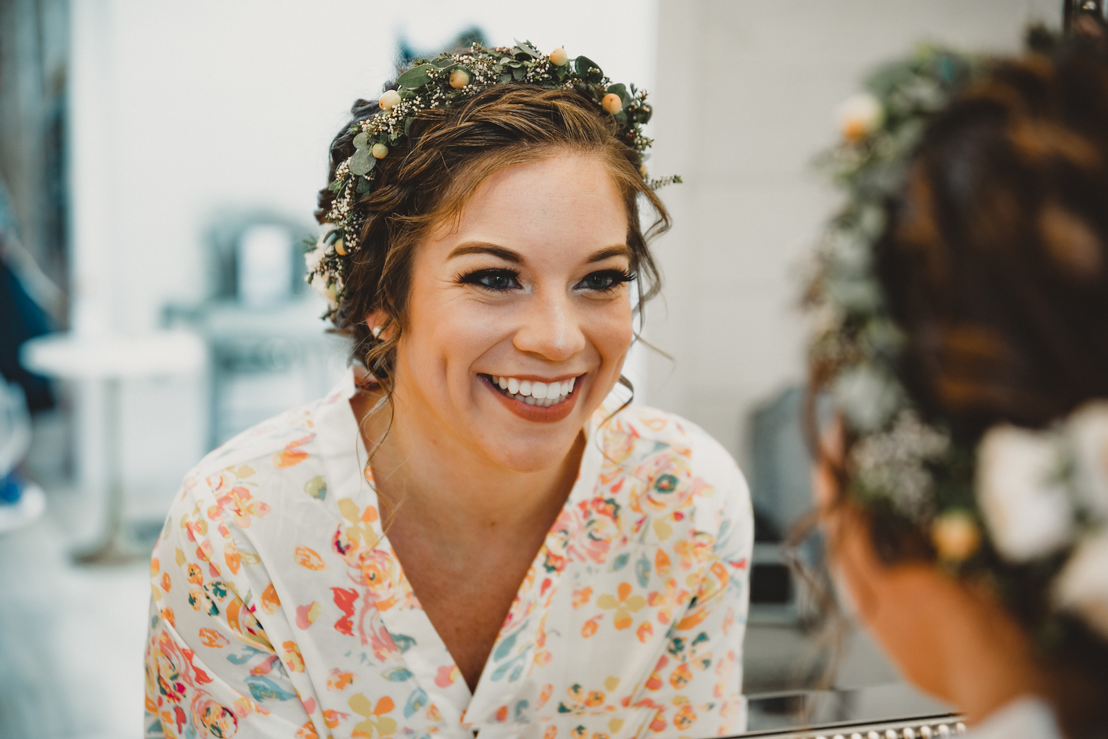 a bride smiling in the mirror while getting ready for her wedding day