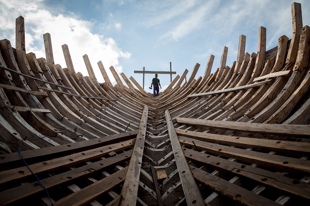 . A Buginese man holds a hammer as he starting to work to install a wooden block in the hull of phinisi at Tanjung Bira Beach on May 2, 2014 in Bulukumba, South Sulawesi, Indonesia.  (Photo by Agung Parameswara/Getty Images)
