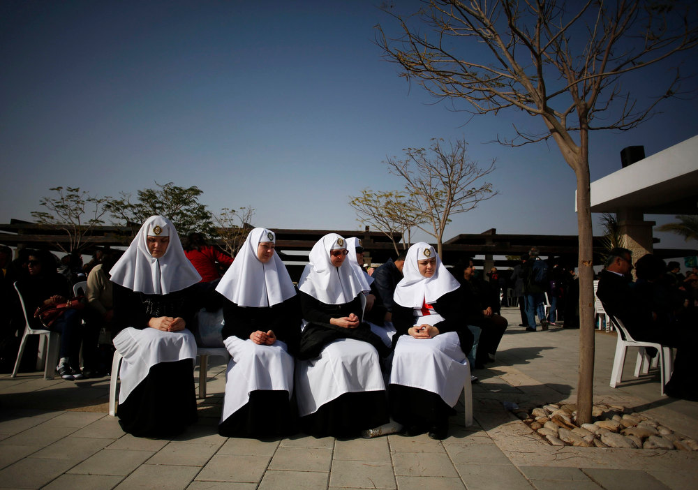 Description of . Orthodox Christian nuns sit during a ceremony at the baptismal site known as Qasr el-Yahud on the banks of the Jordan River near the West Bank city of Jericho January 18, 2013. Over a thousand Orthodox Christians flocked to the Jordan River to celebrate the feast of the Epiphany at the traditional site where it is believed John the Baptist baptised Jesus. REUTERS/Baz Ratner