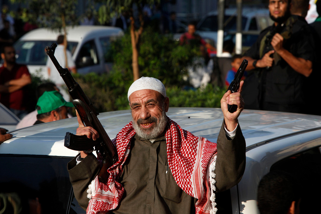 . A Palestinian elderly man holds an AK46 and a pistol as masked Palestinian members of the Ezz Al-Din Al Qassam brigade, the military wing of Hamas, march during a parade to mark the anniversary of a battle against Israel in Gaza City, Thursday, Nov. 14, 2013. (AP Photo/Adel Hana)