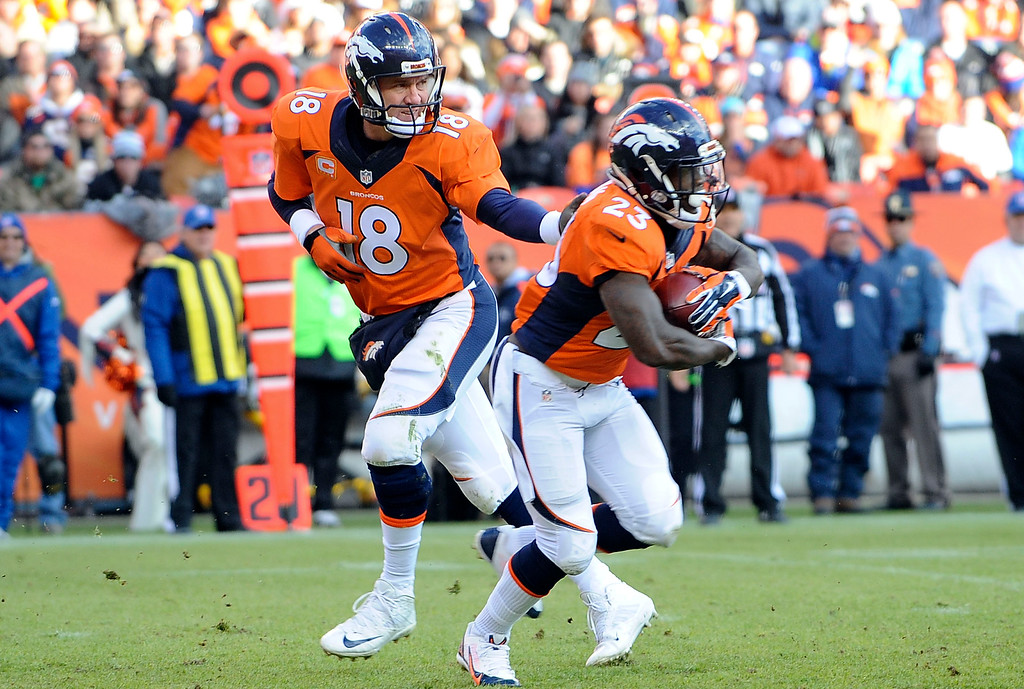 . DENVER, CO - DECEMBER 28: Denver Broncos quarterback Peyton Manning hands off to Ronnie Hillman in the first half against the Oakland Raiders at Sports Authority Field at Mile High in Denver on December 28, 2014. (Photo by Steve Nehf/The Denver Post)