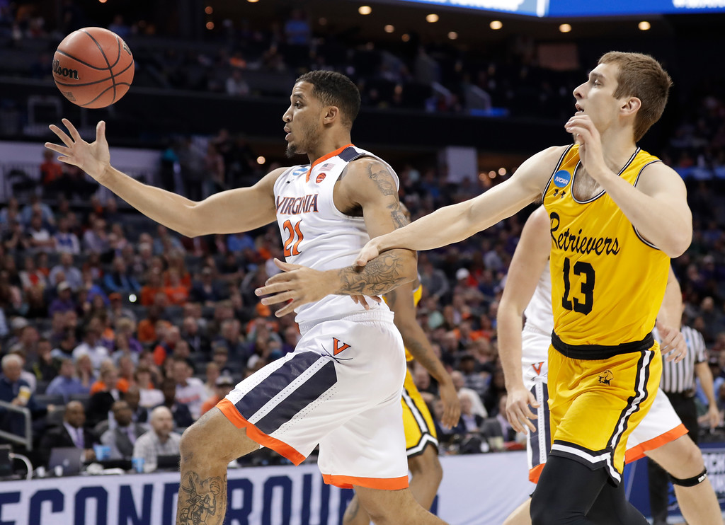 . Virginia\'s Isaiah Wilkins (21) grab a rebound against UMBC\'s Joe Sherburne (13) during the first half of a first-round game in the NCAA men\'s college basketball tournament in Charlotte, N.C., Friday, March 16, 2018. (AP Photo/Gerry Broome)
