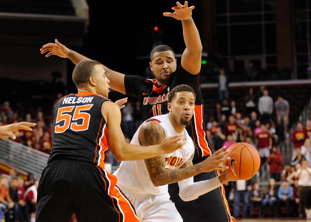 . Oregon State guard Roberto Nelson (55) and forward Joe Burton (11) double team Southern Cal guard J.T. Terrell, center right, during the second half of an NCAA college basketball game, Saturday, Jan. 19, 2013, in Los Angeles. Southern Cal won 69-68. (AP Photo/Gus Ruelas)