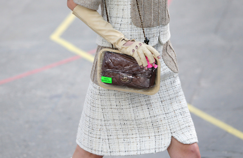 ". A model holds a handbag reading ""100 percent lamb\"" for Chanel\'s ready to wear fall/winter 2014-2015 fashion collection presented in Paris, Tuesday, March 4, 2014. (AP Photo/Jacques Brinon)"