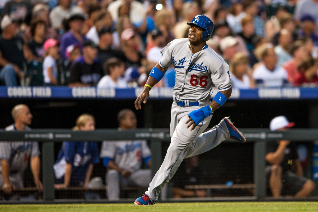 . DENVER, CO - JULY 4:  Yasiel Puig #66 of the Los Angeles Dodgers scores on an Adrian Gonzalez #23 (not pictured) double in the sixth inning of a game against the Colorado Rockies at Coors Field on July 4, 2013 in Denver, Colorado.  The Rockies beat the Dodgers 9-5. (Photo by Dustin Bradford/Getty Images)