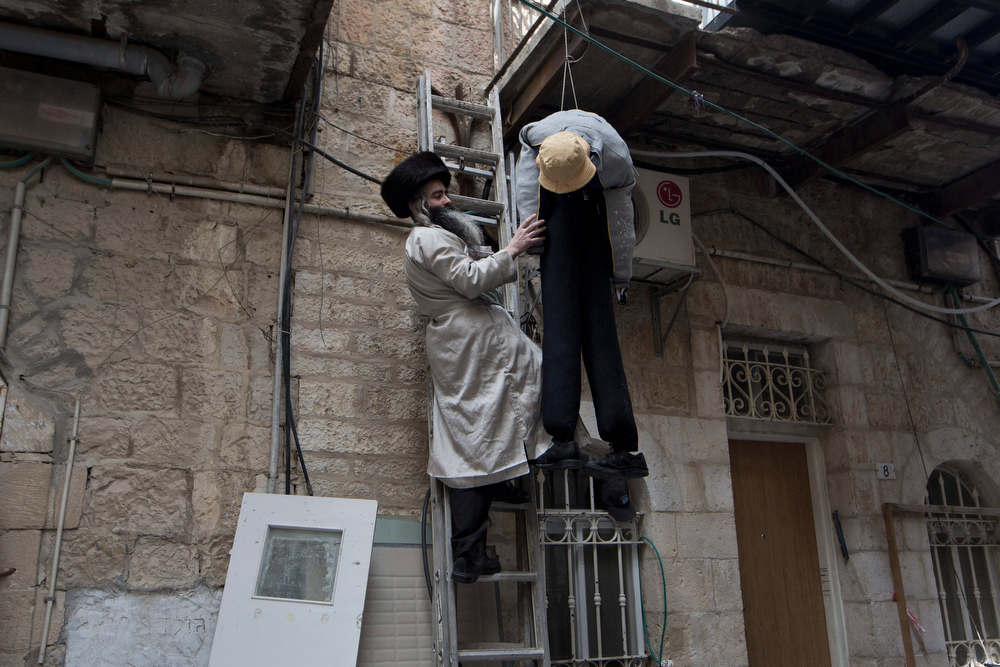 . An Ultra Orthodox Jewish man is seen hanging a doll symbolizing Haman aka \'Haman the Evil\' as part of preparations for the Jewish holiday of Purim in the Mea Shaarim neighborhood in Jerusalem, Israel, 16 March 2014. Haman is a biblical character and vizier of the Persian empire in the 5th century BC that appears in the Book of Esther as the  \'enemy of the Jews\'. The holiday of Purim celebrates the Jews\' salvation from genocide in ancient Persia, as recounted in the Scroll of Esther.  (EPA/ABIR SULTAN)