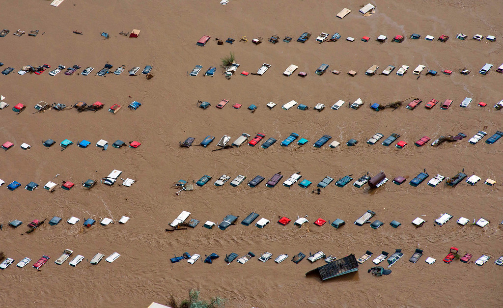 . A field of parked cars and trucks sits partially submerged near Greeley, Colo., Saturday, Sept. 14, 2013, as debris-filled rivers flooded into towns and farms miles from the Rockies. Hundreds of roads, farms and businesses in the area were damaged or destroyed by the floodwaters. (AP Photo/John Wark, File)