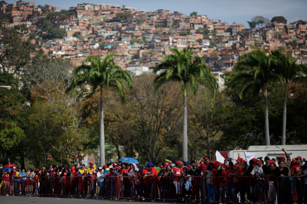 . Mourners line up to view the body of Venezuela\'s late President Hugo Chavez lying in state at the military academy in Caracas on Thursday, March 7, 2013. Battling an unspecified cancer, Chavez died Tuesday. His body was taken to the military academy Wednesday, where he started his army career, his flag-draped coffin lying in state as a mile-long line of mourners came to pay homage Thursday.   (AP Photo/Ariana Cubillos)