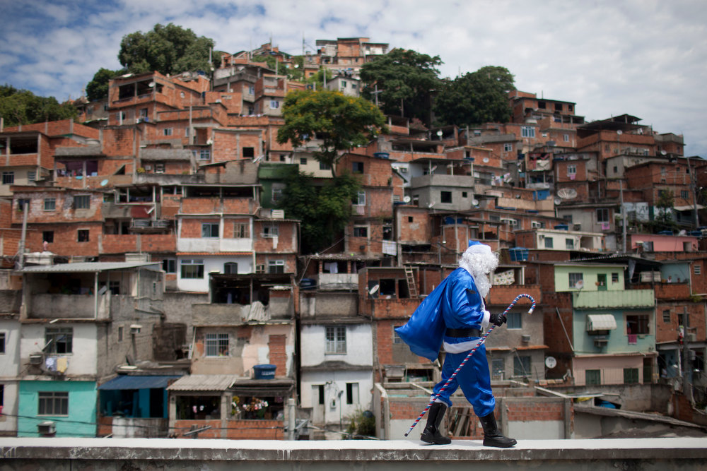 Description of . A police officer dressed in a Santa Claus costume, with the blue color representing the police, walks in Macacos slum after arriving in a police helicopter in Rio de Janeiro, Brazil, Thursday, Dec. 20, 2012. The Pacifying Police Unit, or UPP, organized for Santa to visit the pacified slum to hand out Christmas gifts to young residents. (AP Photo/Felipe Dana)