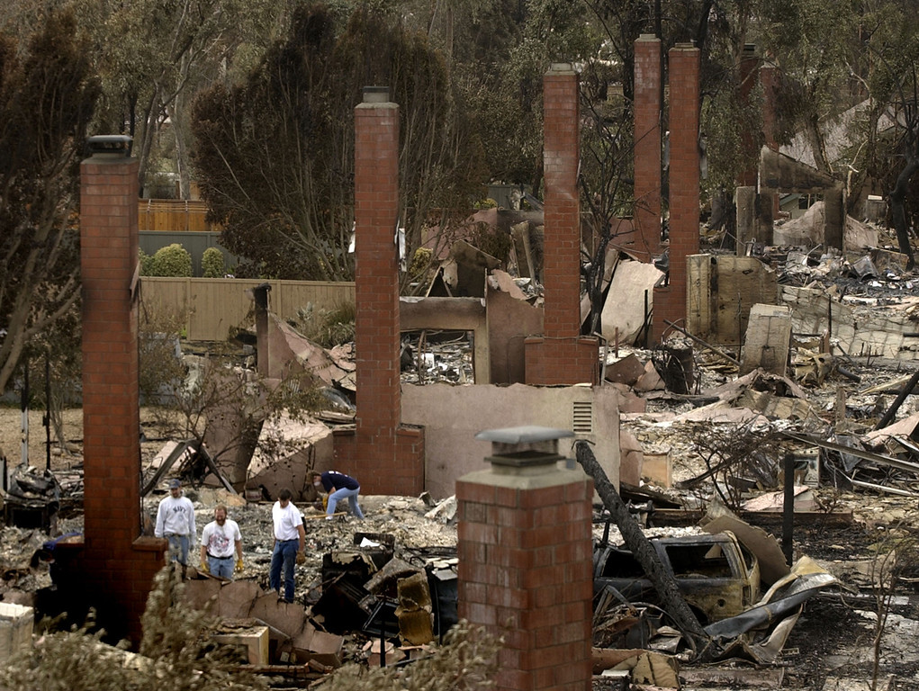 . Chimneys are all that is still standing as residents and friends sort through a charred home in the Scripps Ranch area of San Diego, Calif. Thursday, Oct. 30, 2003. The home was among more than 1,400 lost in the 275,000 acre Cedar fire. (AP Photo/Charlie Riedel)