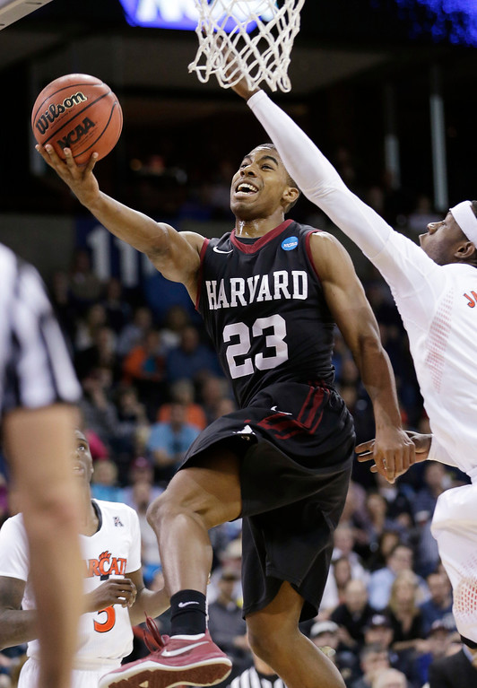 . Harvard\'s Wesley Saunders (23) drives the last past Cincinnati\'s Justin Jackson in the second half during the second round of the NCAA college basketball tournament in Spokane, Wash., Thursday, March 20, 2014. Harvard won 61-57. (AP Photo/Elaine Thompson)