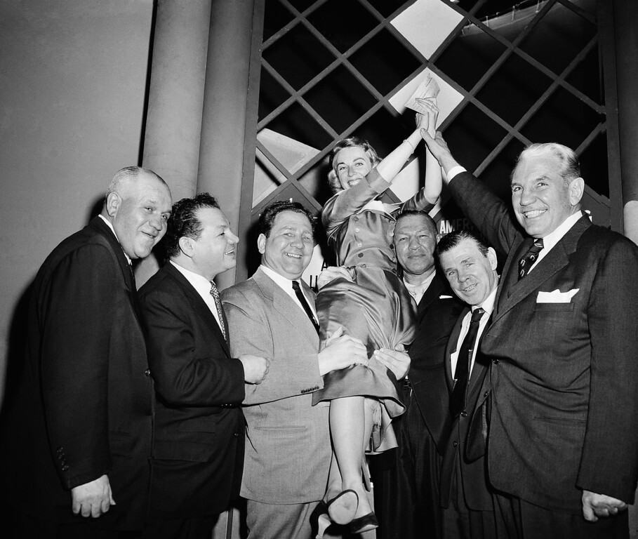 """. Dr. Joyce Brothers, 28-Years old New York Psychologist, is hoisted to shoulders of some of her \""""STAFF\"""" of Boxers after winning top prize on the TV program, \""""The $64,000 Question\"""", in New York City December 6, 1955 with her knowledge of boxing. Left to right are; Marty Sommers, Tony Canzoneri, Gus Lesnevich, Dr. Brothers, Bob Olin, Mickey Walker and Eddie Eagan. (AP Photo)"""