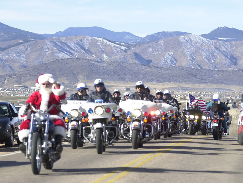 . Santa Claus on his harley leads a pack of riders  in the Rocky Mountain Harley Davison 15th annual Toy Run to  Childrens Hospital which included local police motorcade. The ride started at the Rocky Mountain Harley Davidson store on County Line Rd and  paraded down Broadway to the hospital. This years ride produced more than 1,500 riders who donated 5,000-10,000 toys, 10 t.v. vcr combos, 10 web t.v.\'s and 30 red wagons for the hospital.