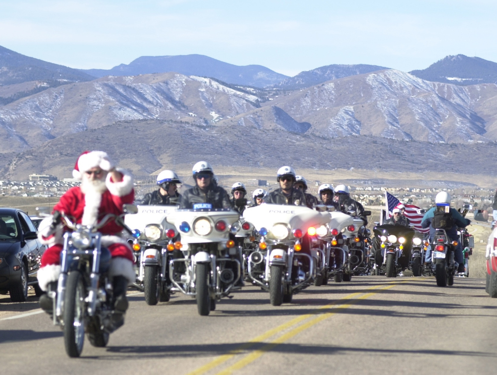 Description of . Santa Claus on his harley leads a pack of riders  in the Rocky Mountain Harley Davison 15th annual Toy Run to  Childrens Hospital which included local police motorcade. The ride started at the Rocky Mountain Harley Davidson store on County Line Rd and  paraded down Broadway to the hospital. This years ride produced more than 1,500 riders who donated 5,000-10,000 toys, 10 t.v. vcr combos, 10 web t.v.'s and 30 red wagons for the hospital.