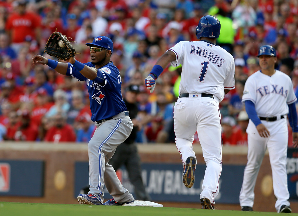 . Toronto Blue Jays\' Edwin Encarnacion reaches out for the throw to first on a ground out by Texas Rangers\' Elvis Andrus (1) in the third inning of Game 1 of the American League Division Series baseball game, Thursday, Oct. 6, 2016, in Arlington, Texas. (AP Photo/LM Otero)