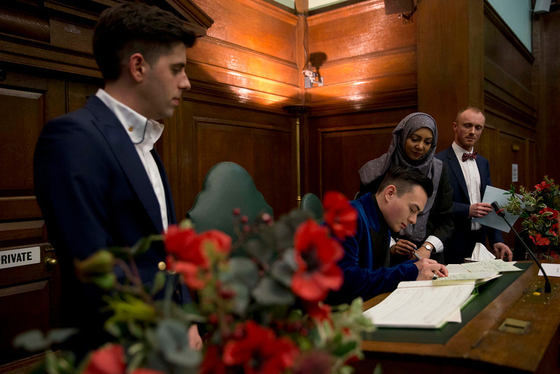 . Sinclair Treadway signs the documentation watched by his husband Sean Adl-Tabatabai, left, after they were officially married in a wedding ceremony in the Council Chamber at Camden Town Hall in London, minutes into Saturday, March 29, 2014.  Gay couples in Britain waited decades for the right to get married. When the opportunity came, some had just days to plan the biggest moment of their lives. Adl-Tabatabai, a 32-year-old TV producer from London, and Treadway, a 20-year-old student originally from Los Angeles, registered their intent to marry on March 13, the first day gay couples could sign up for wedding ceremonies under Britain\'s new law. Eager to be part of history, the two men picked the earliest possible moment - just after midnight Friday, when the act legalizing same-sex marriage takes effect.  (AP Photo/Matt Dunham)