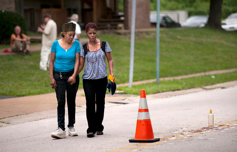 . Tammy Miles, left, and Janice Battle hold hands as they take a closer look at the scene where Michael Brown, 18, was shot in Ferguson, Mo., Sunday, Aug. 10, 2014. Brown died following a confrontation with police, according to St. Louis County Police Chief Jon Belmar, who spoke at a news conference Sunday. (AP Photo/Sid Hastings)