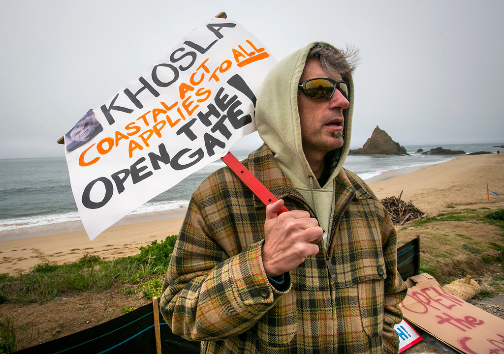 . Activist Mike Wallace, of Moss Beach, carries sign during a protest at  Martin\'s Beach in Half Moon Bay, Calif., on Thursday, March 14, 2013. Martin\'s Beach was closed to public access in 2008 when the property was purchased by venture capitalist Vinod Khosla. Former California Congressman Pete McCloskey joined members of the Surfrider Foundation and other public activists for a protest outside the gate to Martin\'s beach for public access to the beach to be restored. On Tuesday, the Surfrider Foundation filed suit a law suit citing the beach closure is in violation of the California Coastal Act. (John Green/Staff)
