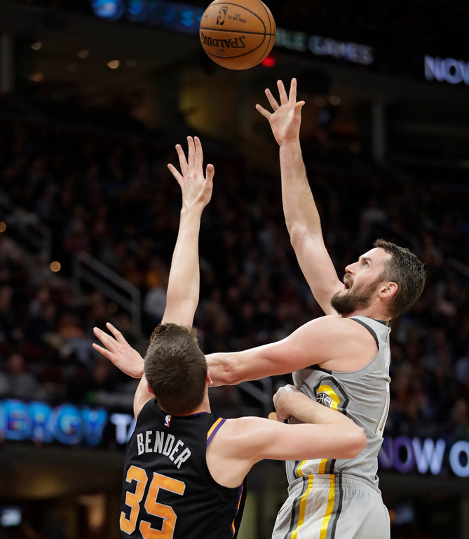. Cleveland Cavaliers\' Kevin Love, right, shoots over Phoenix Suns\' Dragan Bender (35) in the second half of an NBA basketball game, Friday, March 23, 2018, in Cleveland. (AP Photo/Tony Dejak)