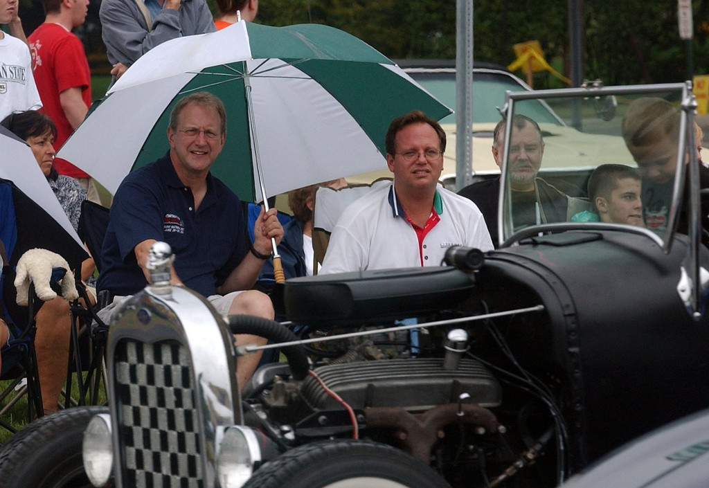 . (from left) Dick Roth, of Shelby Twp. and Dean Didion, of Clarkston, stay dry while watching the classic cars cruise Woodward Ave. in Royal Oak during the 2006 Woodward Dream Cruise.