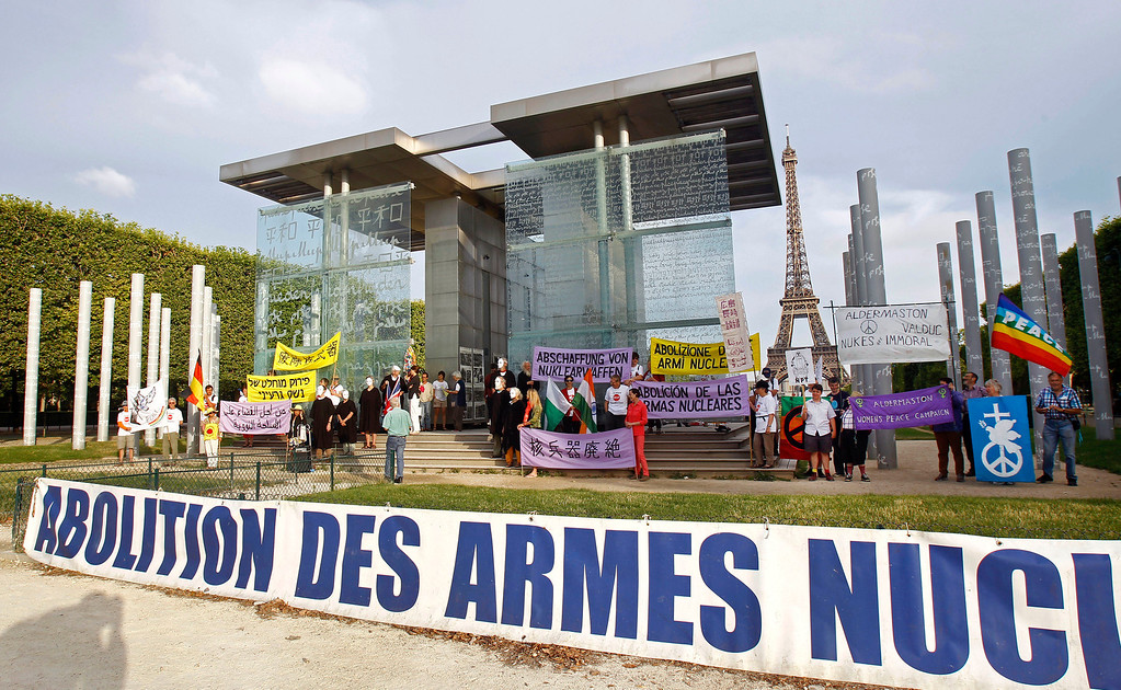 """. Pacifist militants stage a commemorative demonstration at the Peace Wall in Paris, Tuesday Aug. 6, 2013, to mark the 68th anniversary of the atomic bombing of Hiroshima. The sign in the foreground reads \""""Abolition of Nuclear Weapons.\"""" (AP Photo/Remy de la Mauviniere)"""