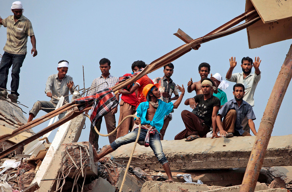 . Bangladeshi rescue workers gesture to communicate with other rescuers at the site of a building that collapsed Wednesday in Savar, near Dhaka, Bangladesh, Thursday, April 25, 2013. (AP Photo/A.M. Ahad)