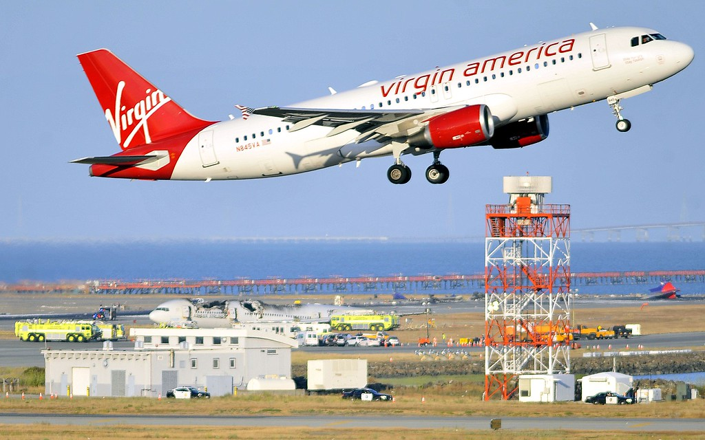 . A Virgin America flight takes off while a crashed Asiana Airlines Boeing 777 is seen on the runway at San Francisco International Airport on Saturday, July, 06, 2013.  At least two people were killed and 130 injured when an Asiana Airlines Boeing 777 jet crashed and caught fire as it landed short of the runway. It was not immediately clear if those people were presumed dead or had left the scene without alerting officials. (Josh Edelson/AFP/Getty Images)