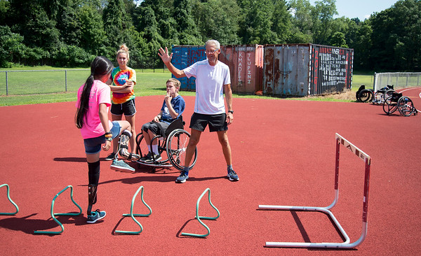 08/08/19 Wesley Bunnell | Staff Track and Field coach Bill Wilkie, center, demonstrates proper technique for warming up to campers including Sarah Reid at the Hospital for Special Care's Ivan Lendl Adaptive Sports Camp at Berlin High School on Thursday August 9, 2019.