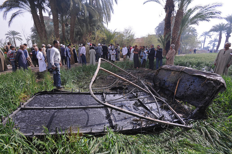 . Egyptians gather at the site of a balloon crash where the remains of the burned gondola are seen, outside al-Dhabaa village, just west of the city of Luxor, 510 kilometers (320 miles) south of Cairo, Egypt, Tuesday, Feb. 26, 2013. A hot air balloon flying over Egypt\'s ancient city of Luxor caught fire and crashed into a sugar cane field on Tuesday, killing at least 18 foreign tourists, a security official said. The casualties included French, British, Belgian, Hungarian, Japanese nationals and nine tourists from Hong Kong, Luxor Governor, Saad told reporters. (AP Photo/Hagag Salama)
