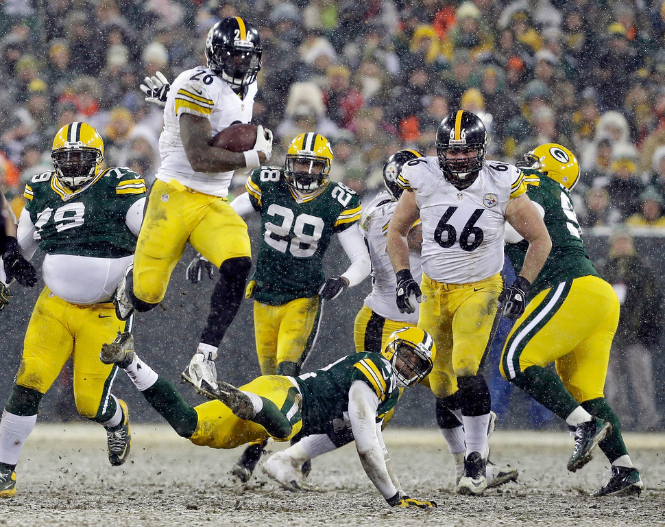. Pittsburgh Steelers\' Le\'Veon Bell (26) leaps over Green Bay Packers\' Morgan Burnett during the second half of an NFL football game Sunday, Dec. 22, 2013, in Green Bay, Wis. (AP Photo/Mike Roemer)