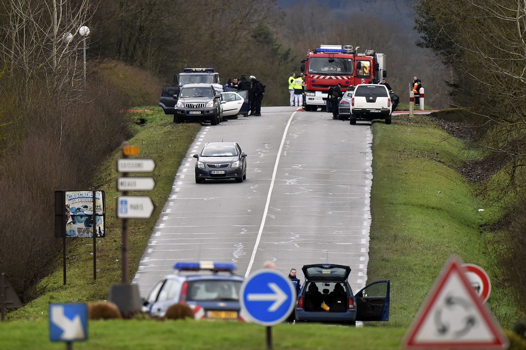 . French police and a fire truck are seen on a road in Dammartin-en-Goele, north-east of Paris, where two brothers suspected of slaughtering 12 people in an Islamist attack on French satirical newspaper Charlie Hebdo held one person hostage as police cornered the gunmen, on January 9, 2015. The hostage drama unfolded at a printing business in the small town of Dammartin-en-Goele, only 12 kilometers (seven miles) from Paris\'s main Charles de Gaulle airport, police sources said. AFP PHOTO / DOMINIQUE  FAGET/AFP/Getty Images
