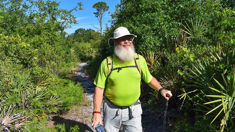 John hiking through scrub forest