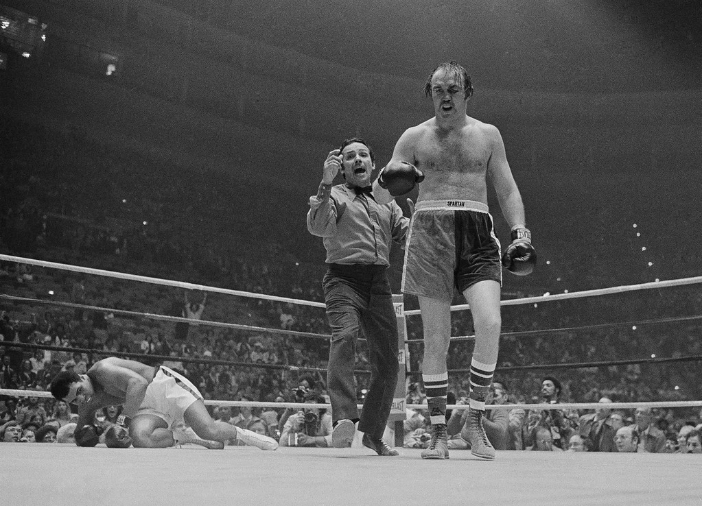 . Heavyweight champion Muhammad Ali starts to get to his feet as referee Tony Perez sends Chuck Wepner to a neutral corner after Ali was knocked down in the ninth round of title bout at Cleveland Coliseum in Richfield, Ohio, March 24, 1975. Ali won with a knockout in the 15th round. (AP Photo/Charles Knoblock)