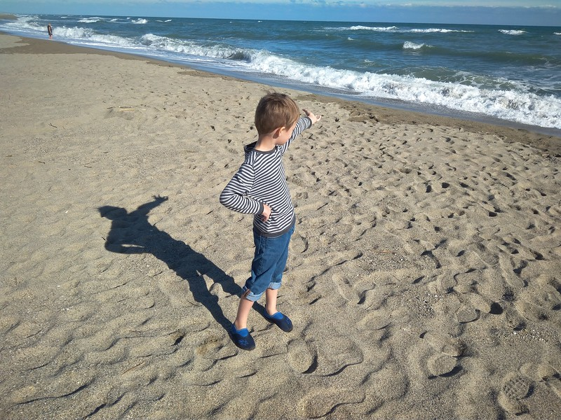 Boy standing on beach in France.