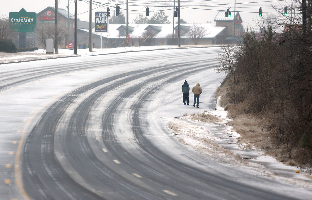 """. Two people walk along an empty Jimmy Carter Boulevard Wednesday, Feb. 12, 2014, in Norcross, Ga. Across the South, residents woke up Wednesday to a region encased in ice, snow and freezing rain, with forecasters warning that the worst of the potentially \""""catastrophic\"""" storm is yet to come.  (Photo/Jason Getz)"""