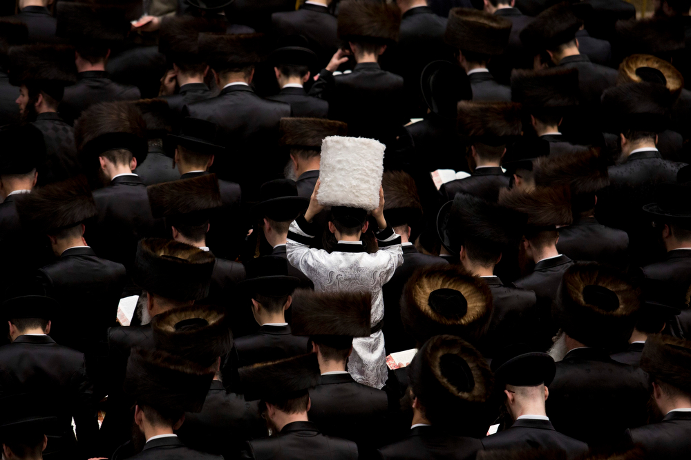 . An Ultra Orthodox Jewish child wearing white (C) stands among men reading from the Book of Esther during a prayer for the Jewish Holiday of Purim in the Mea Shaarim neighborhood in Jerusalem, Israel, 16 March 2014. The joyful Jewish holiday of Purim celebrates the Jews\' salvation from genocide in ancient Persia, as recounted in the Scroll of Esther.  (EPA/ABIR SULTAN)