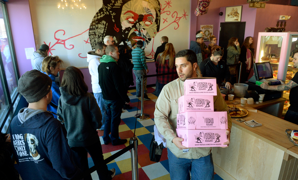 . Lawrence Rimbert carries out 4 dozen doughnuts from Voodoo Doughnut, a new business from Oregon,  as it held its grand opening on Wednesday, January 15, 2014. Denver Mayor Michael Hancock was on hand to welcome Voodoo to town. (Denver Post Photo by Cyrus McCrimmon)