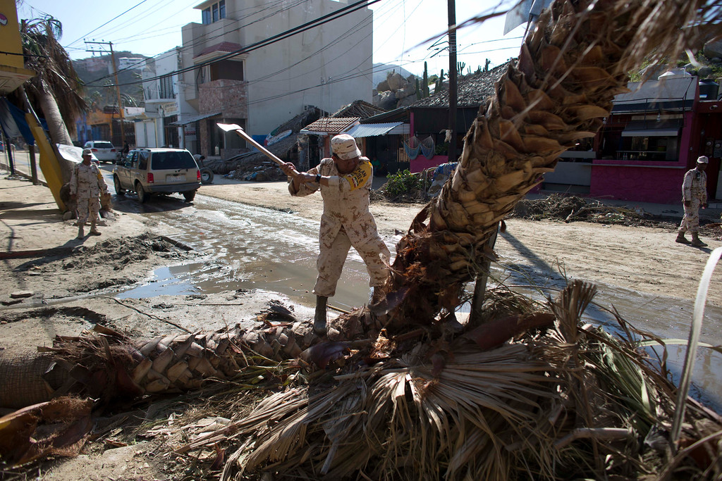 . A Mexican army soldier uses an axe on a palm tree felled when Hurricane Odile made landfall as a Category 3 storm,  in Cabo San Lucas, Mexico, Thursday, Sept. 18, 2014. As clean up began, water and electricity service remained out and phone service intermittent. Electric commission officials said some 2,500 power poles were toppled by Odile, which struck late Sunday, leaving widespread damage and flooding. (AP Photo/Dario Lopez-Mills)
