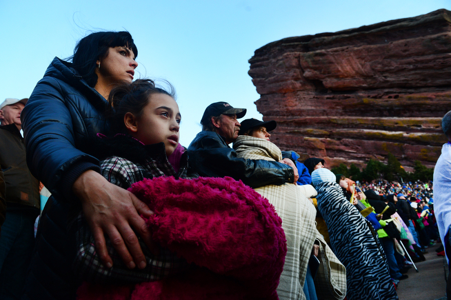 """. Carey Meinert, left, holds her daughter Lucy, 9, as the two enjoy  the 67th annual Easter sunrise service  at Red Rocks Amphitheatre in Morrison, Co on April 17, 2014.  Superintendent Patrick L. Demmer gave the sermon which was entitled \""""What are you looking for?\"""".  The popular annual event, which hosts thousands of worshippers, is sponsored by the Colorado Council of Churches.  (Photo By Helen H. Richardson/ The Denver Post)"""