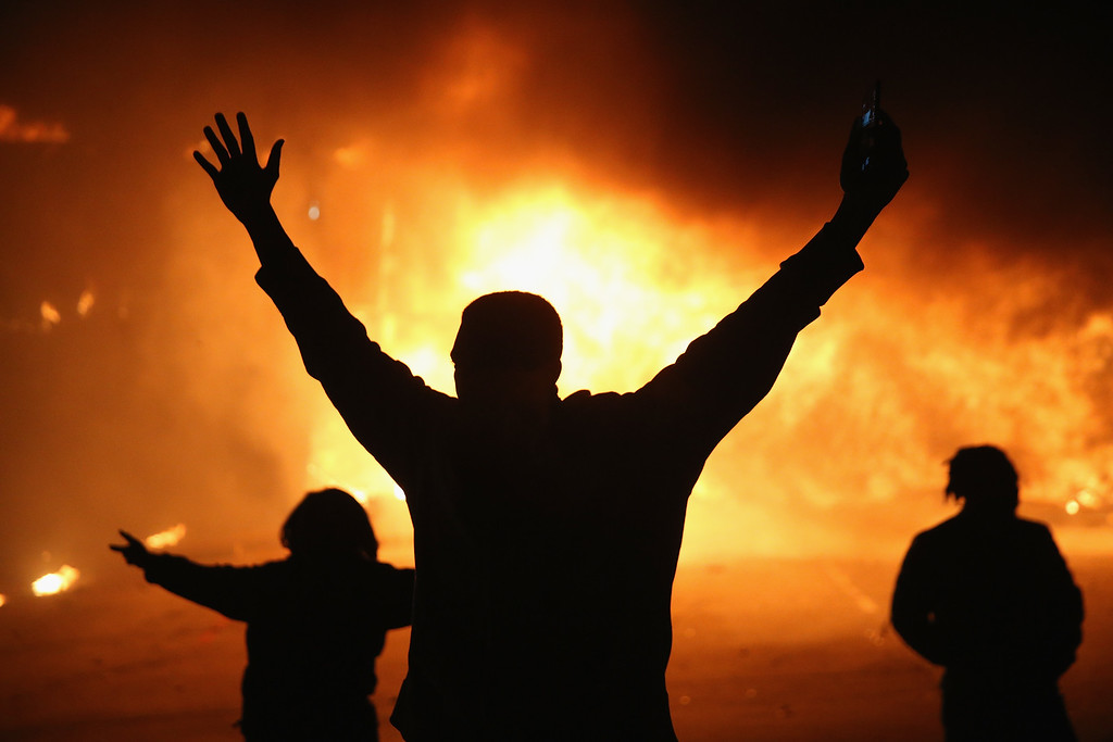 . Demonstrators celebrate as a business burns after it was set on fire during rioting following the grand jury announcement in the Michael Brown case on November 24, 2014 in Ferguson, Missouri. Ferguson has been struggling to return to normal after Brown, an 18-year-old black man, was killed by Darren Wilson, a white Ferguson police officer, on August 9. His death has sparked months of sometimes violent protests in Ferguson. A grand jury today declined to indict officer Wilson.  (Photo by Scott Olson/Getty Images)