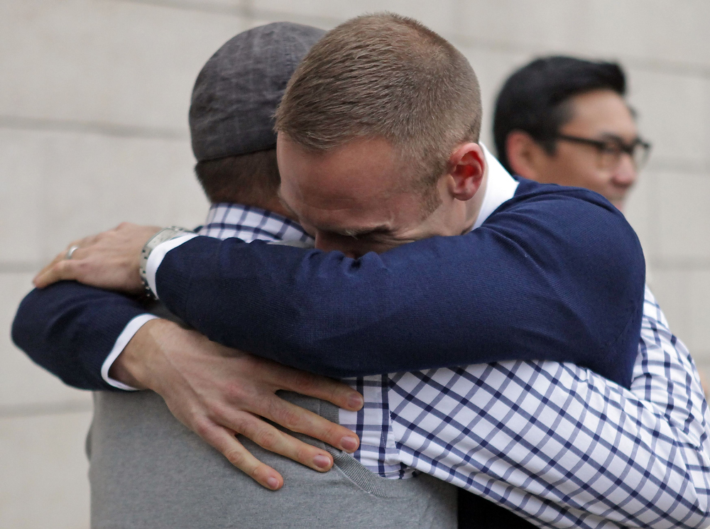 . Bernie Liang (L), and Ryan Hamachek embrace after getting married outside Seattle City Hall in Seattle, Washington December 9, 2012. Washington made history last month as one of three U.S. states where marriage rights were extended to same-sex couples by popular vote, joining Maryland and Maine in passing ballot initiatives recognizing gay nuptials.  REUTERS/Cliff Despeaux